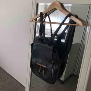 Svart liten ryggväska med guldfärgade detaljer. Använt ett par gånger. Fortfarande i bra skikt. Kontakta för fler bilder och frågor! Frakt förekommer.