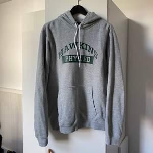 Grå hoodie från Nike x Stranger Things. Använd fåtal gånger, väldigt bra skick. Storlek M.