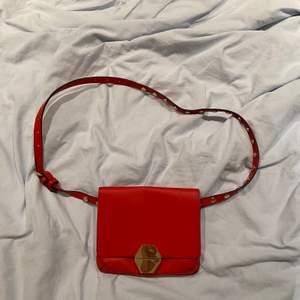 En röd väska med guldiga detaljer som funkar som både magkänsla och axelväska. Väskan är från Zara och priset är 70kr ❤️:)