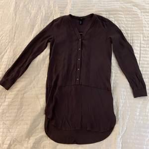 Mörkgrå långärmad klänning från H&M i strl 36. Färgen skiftar lite i brunt. Fina detaljer och i fint skick. Aldrig använd.