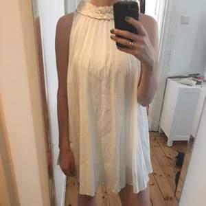 Vit plisserad klänning med paljetter runt halsen. Köpt second hand på Lisa Larsson i Stocholm