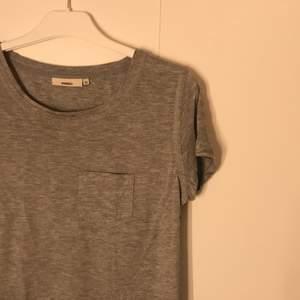 grå tshirt med sydda detaljer och ficka. säljer för 10kr + frakt