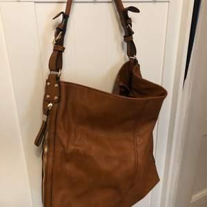 Brun läderväska med guldiga detaljer