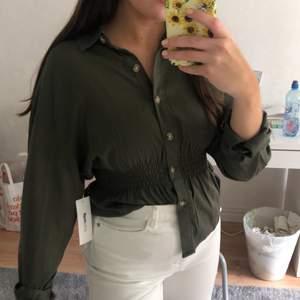 En militärgrön skjorta från Gina Tricot med smock detalj i midjan, för att skapa en fin figur. Strl 36. Helt oanvänd med prislapp kvar. Köpt för 350kr men säljer för 250kr + frakt. Önskas fler bilder är det bara att hojta till🌸
