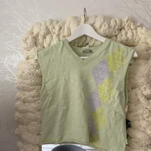 En argyle inspirerad tröja som jag klippt av ärmarna och nedre delen på så den är väll numera en väst, använts en gång men inget mer än då, köparen står för frakt