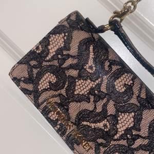 Plånboksväska från Victoria secret! Går att använda som en liten väska men kedjan kan även tas bort så den kan användas som plånbok! Många korthållare och även hållare för mobil🥰 mycket fint skick! 🥰 pris kan diskuteras då jag vill bli av med den!