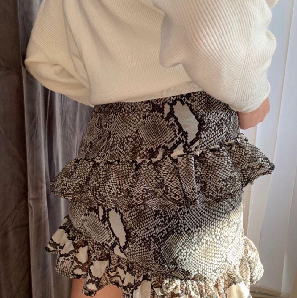 Kort kjol i ormskinnsmömster med gulliga volanger, använd 1-2 ggr. Kjolar.