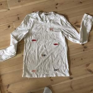 T-shirt med långa ärmar från Monki. Broderade tryck. Använd en gång. (Obs, ej struken på bild!).