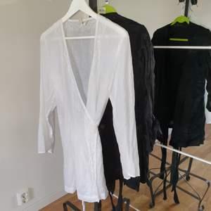 Omlott topp eller kort klänning med brodyr på framsidan finns i både svart eller vit linne