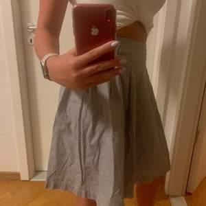 Supersöt knälång kjol från okänt märke (frk.) i strl 38 säljs då den är förstor för mig. Den är i skjortmaterial med små små ränder i vit och mörkgrå/svart. Pris exkl frakt