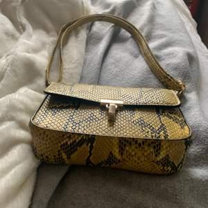 Super fin handväska med ormskinnsmönster och gulddetaljer. Knappt använd och ser ut som ny. Kostar 100kr