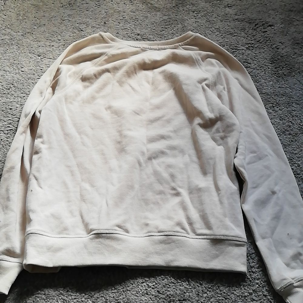En beige/sandfärgad sweatshirt med tryck. Det står