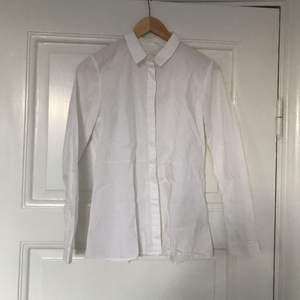 Vit bomullsskjorta från Cos med söm i midjan för fin passform