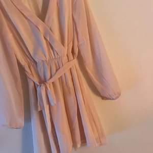 Ljus rosa klänning ifrån nelly. Aldrig använd. Kan mötas upp i Stockholm eller så står köparen för frakten!