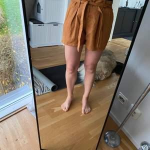 Mörkt orangea shorts i mockaimitation (100% polyester) som knyts med midjeband. Jättebra skick, knappt använda. Ganska stora i storleken, passar 38a.