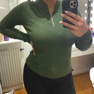 Snygg grön tröja med dragkedja. Framhäver formerna