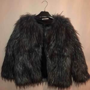 En blå/svart fuskpälsjacka med en ficka på vardera sida. Använd ca 3 gånger och är i lika fint skick som när jag köpte den.