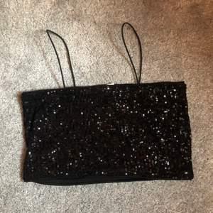 Svarta paljetter med smala straps. Köpt från hm till nyår men kom aldrig till användning. Storlek small
