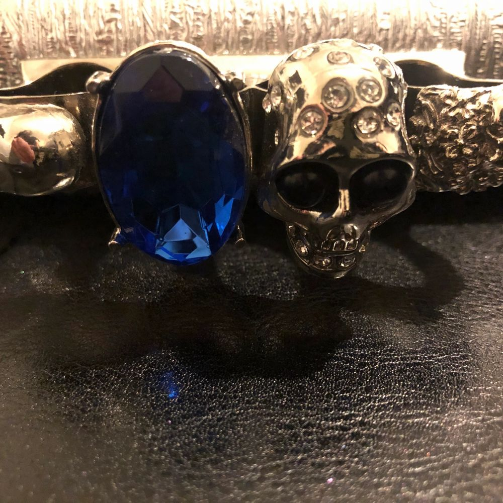 Ring väska silvrig med dödskallar och en royal blå Sten . Väskor.
