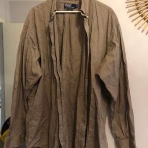 En snygg beige / brun beige skjorta från Ralph lauren. Helt oanvänd. Frakt tillkommer! Frakten står längre ner i posten.