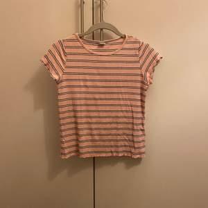 Rosa randig T-shirt i nyskick. Pris 50kr frakt tillkommer storlek kids 158/164 kontakta vid intresse☺️
