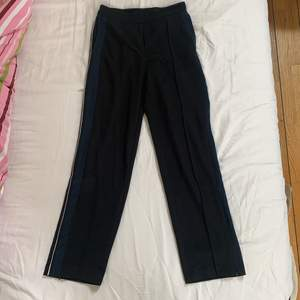 Svarta kostymbyxor från Monki med blå rand på sidorna och även en  smal vit rand. Finns blixtlås nere vid byxbenet så man kan öppna och då få en sorts slits. Storlek 36