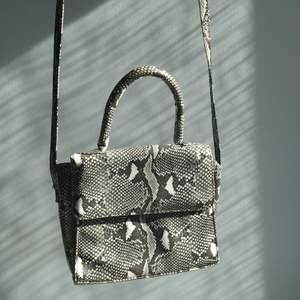 Svinball väska som är i ett läderliknande material med ormskinnsmönster