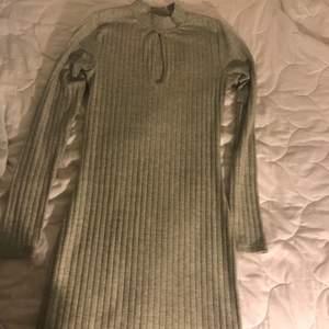 En fin grå klänning med en urring. Säljs bara i Helsingborg. Från Bik bok. Sitter väldigt fin på kroppen.