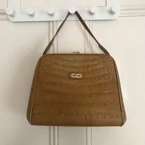 Gul vintage mellanstor väska. Platt och stabil botten vilket gör väskan väldigt rymlig. Kort handtag och guldiga detaljer och knäppe. Aldrig använd. Frakt tillkommer.