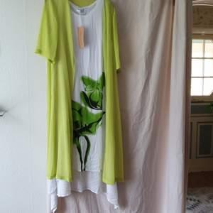 Helt ny sommarklänning i vitt med grönt blommönster. Den ljusgröna med ärm är avtagbar.
