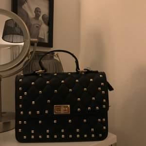 Säljer en valentino imitation, svart med guldiga detaljer & knappt använd, materialet är i skinn och finns även en guldig kedja till