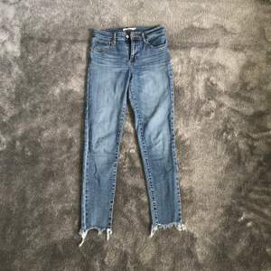 Säljer ett par blå Levis jeans i modell 721 med slitningar nertill. Använda men i bra skick. Storlek 26. Skriv för fler bilder.