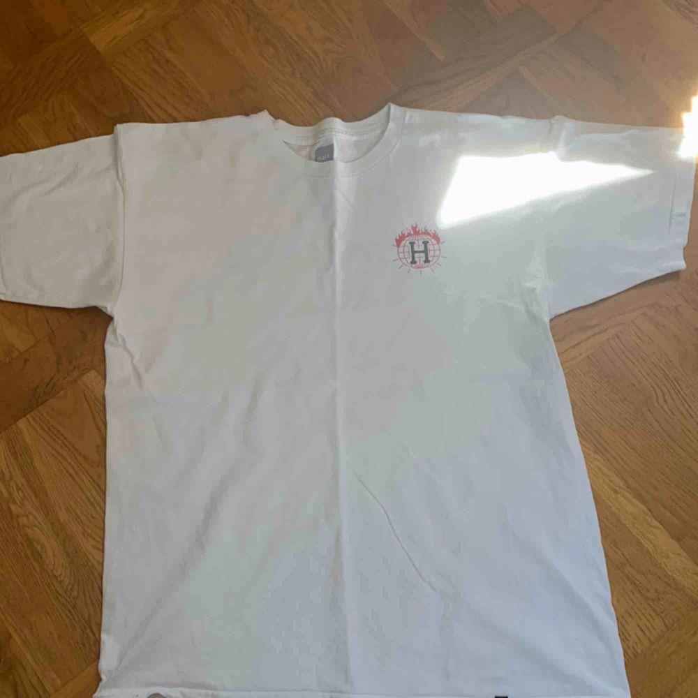 Thrasher x Huf t shirt med logga på ryggen. Bra skick men ett litet hål på ryggen som knappt syns. T-shirts.