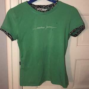 (Frakten är inräknad i priset) Säljer denna gröna retro moshino jeans t shirten med fina detaljer köpt second hand storlek xs men den ör stretchig så passar som s med. Det är ett litet hål på sidan men inget som man lägger märke till annars i bra skick. Tycker om den väldigt mycke så gör lite ont att sälja den därav priset men det är bara att höra av sig vid minsta fråga eller intresse💚
