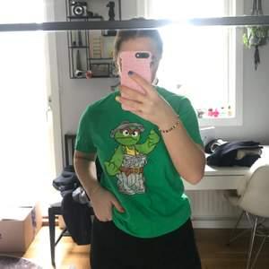 Grön T-shirt med tryck från sesame street. Väldigt bra skick. Köparen står för frakt.