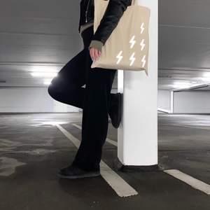 Beige tygväska tillverkad i 100% bomull med ett tryck bestående av 6 blixtrar i en silverfärgad reflex. Centrerat på baksidan är även vår logotyp tryckt i silverfärgad reflex.