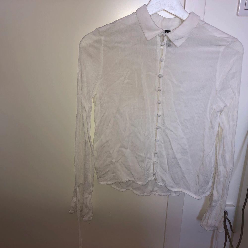 En somrig, vit skjorta i skönt bomullsmaterial. Går att öppna och stänga (beror lite på hur man själv vill styla den). Det finns även söta detaljer längs händerna. . Blusar.