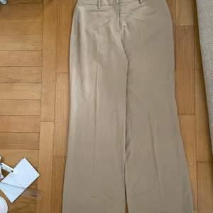 Ett par beiga kostymbyxor i storlek 38