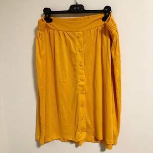 Senapsgul oanvänd kjol i mjukt material. Storlek XL men passar även en storlek L. Köpt för 349 kr.