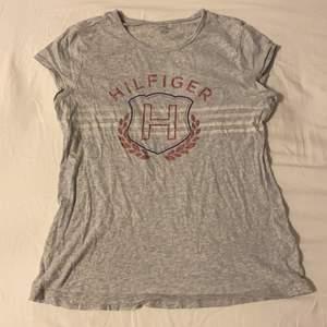 Grå Tommy hilfiger t-shirt med rosa shimrigt, vitt, blått tryck. Köpt i usa! Storlek XL/ 16 år i barnstorlek( jag är en S). 60 kr + 60kr frakt
