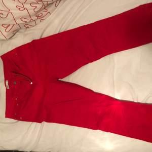 Röda utsvängda jeans med detalj av avklippning nedtill. Aningen små för mig därav säljer jag de.