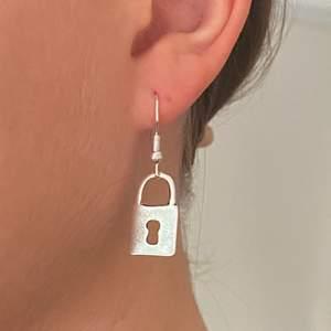 Örhängen i form av hänglås. Örhängena är nickelfria! Pris: 49 + 11 kr frakt. Finns 3/3 i lager!