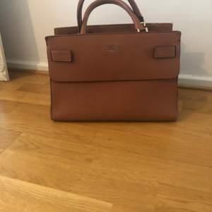 Brun Guess väska, använd och har normal slitage.