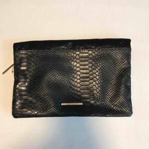 Riktigt snygg clutch väska! Svart med krockodilmönster och gulddetaljer. Rymmer allt det viktiga man behöver när man ska iväg, mobil, plånbok, nycklar, hörlurar, mindre necessär osv. Väldigt rymlig för att vara en mindre väska! Mycket fint skick!