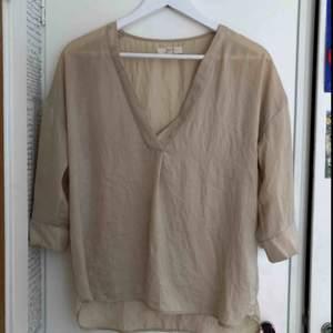 Sandfärgad trekvartslång blus i typ silke!