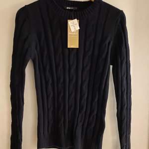 En helt oanvänd stickad tröja ifrån Gina Tricot i färgen mörkblå.