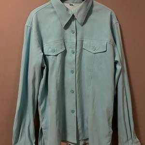 Säljer denna ljusblå/gröna overshirt/skjortan, den har en snygg spetsig krage med två fickor över brösten.