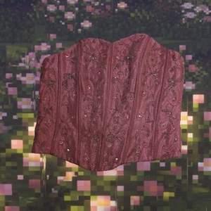 Jättefin rosa korsett top med mönster av pärlor i ett glansigt material💕 Toppen har ingen ihopsnörning, istället stänger man med en dragkedja som sitter på ryggen! Den finns ingen lapp, men den passar s och medium bäst.                                      Jag kan mötas upp i Stockholm och annars står köparen för frakten🥰