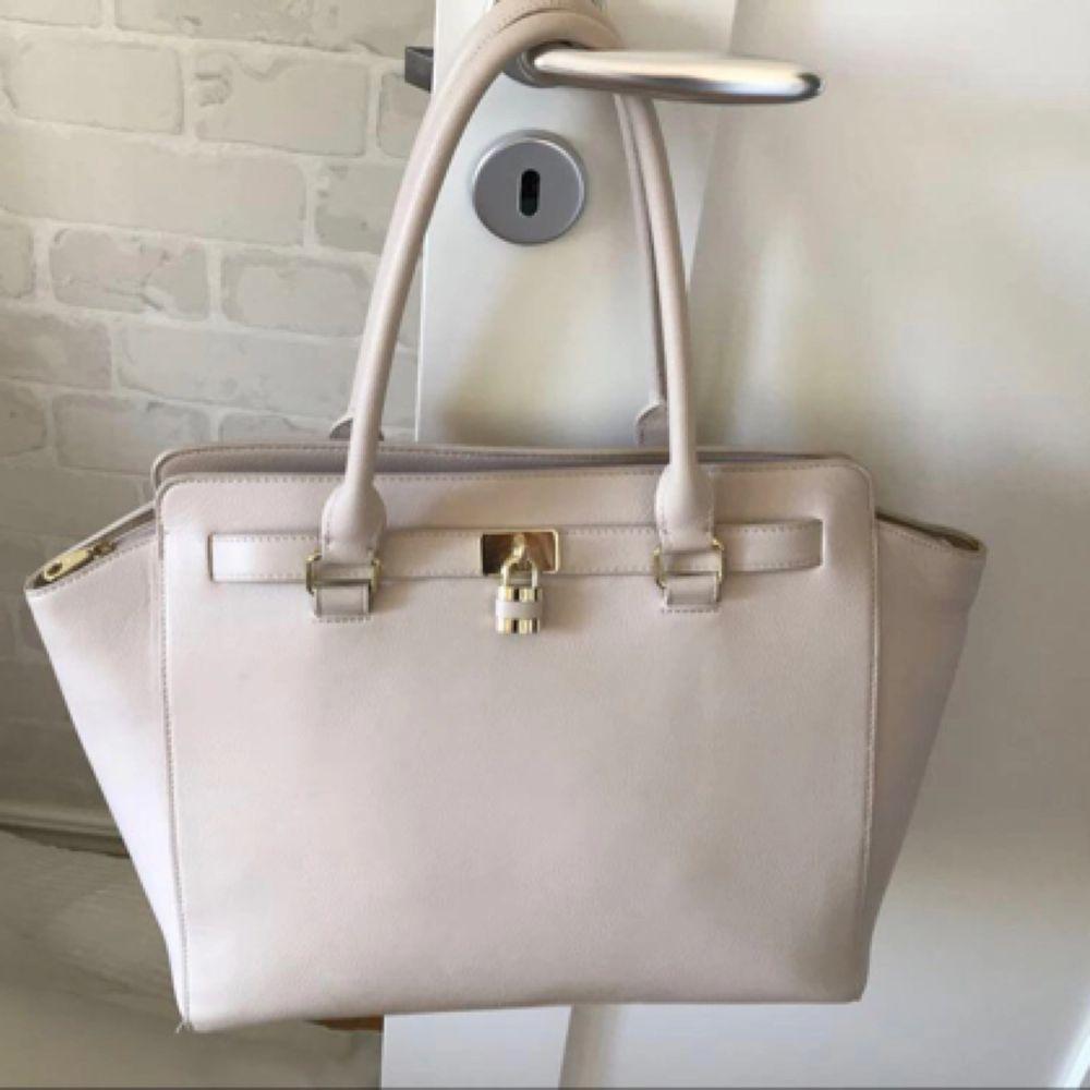 Don Donna handväska i bra skick. Handväskan är i färgen beige och har gulddetaljer och axelband. Vill du ha mer bilder på väskan är det bara att fråga :) Ordinarie pris: 435 kr. Väskor.
